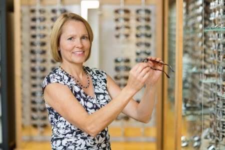 Portrait of happy mature woman selecting glasses in optician store photo