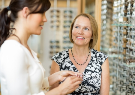 salesgirl: Happy senior woman with salesgirl selecting glasses in optician store Stock Photo