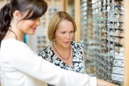 salesgirl: Salesgirl assisting senior woman in selecting glasses at optician store Stock Photo