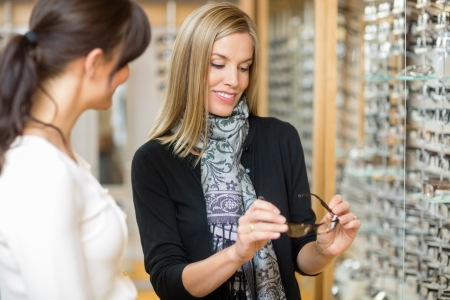 salesgirl: Young woman examining eyeglasses with salesgirl in optician store
