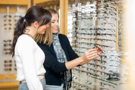 salesgirl: Happy woman with salesgirl examining eyeglasses in optician store
