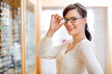 trying on: Portrait of beautiful young woman trying new glasses in optician store Stock Photo