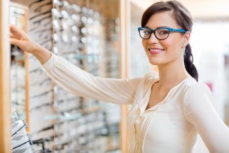 Portret van gelukkige jonge vrouw kopen van een nieuwe bril bij opticien winkel Stockfoto