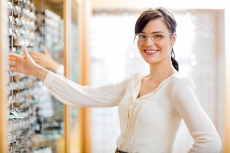 Portrait of happy female customer buying new glasses at optician store photo