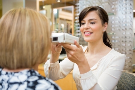 Young female optometrist measuring pupilary distance on senior customer