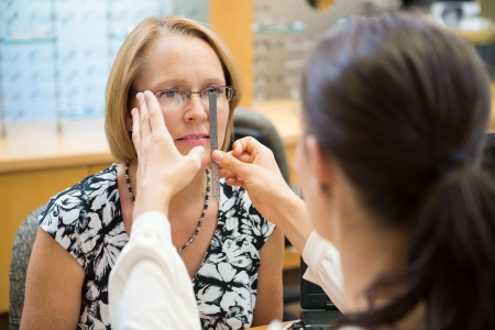 Female optician measuring mature womans eyeglasses in store photo