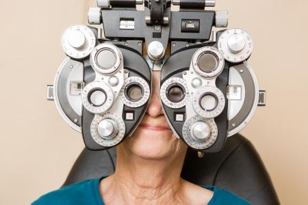 eye exam: Senior woman looking through phoropter during eye exam Stock Photo