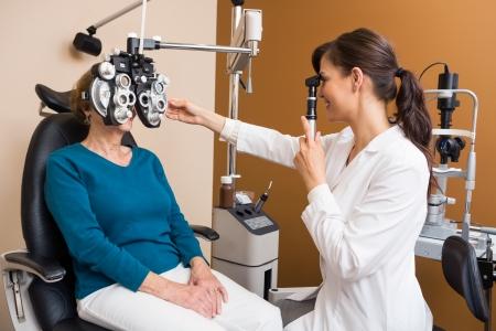 Jonge vrouwelijke optometrist onderzoekt de ogen van senior vrouw in winkel