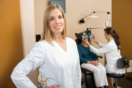 mid adult female: Portrait of mid adult female eye doctor with colleague examining patient in background
