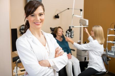 oculista: Retrato de joven especialista de los ojos con el colega que examinan al paciente en el fondo