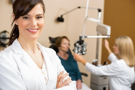 oculist: Portrait of female optometrist with colleague examining patient in background