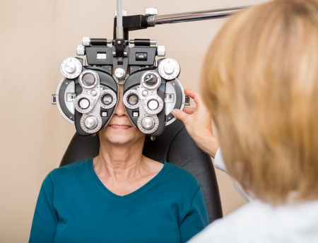 detect: Female ophthalmologist using phoropter to check a senior womans eyes