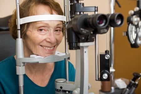 slit: Sonriente mujer sometida a prueba de examen de la vista superior con l�mpara de hendidura en la tienda Foto de archivo
