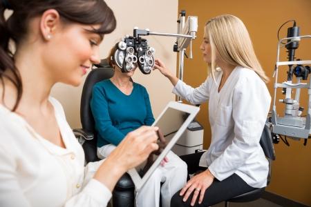 Mujer optometrista examina los ojos de la mujer de edad mientras colega que usa la tableta digital en tienda