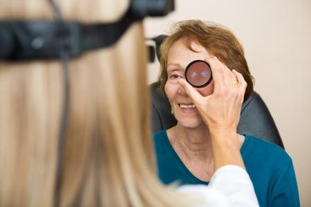 Female optician examining senior womans eye with binocular indirect ophthalmoscope