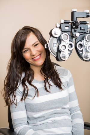 Portrait of beautiful young woman sitting behind phoropter during eye exam photo