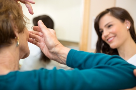 Senior woman inserting contact lens in optician store photo