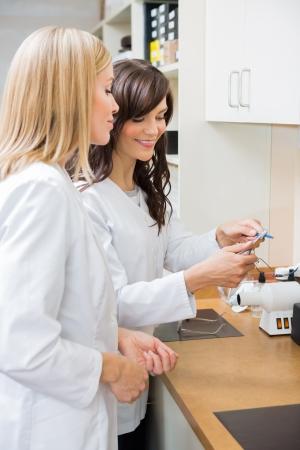 Female opticians repairing glasses in workshop photo