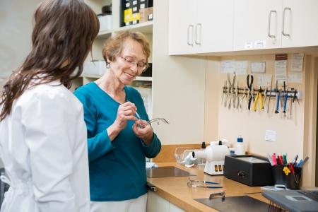 apprentice: Senior optician with apprentice repairing glasses with screwdriver in workshop