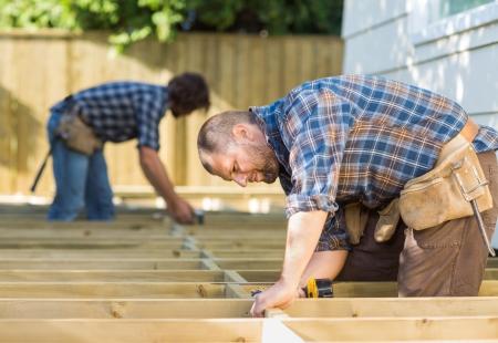 Zijaanzicht van de tussentijdse volwassen timmerlieden werken op bouwplaats