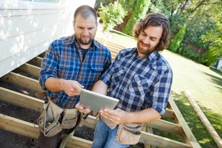 Mid volwassen arbeiders bespreken project over digitale tablet op bouwplaats Stockfoto