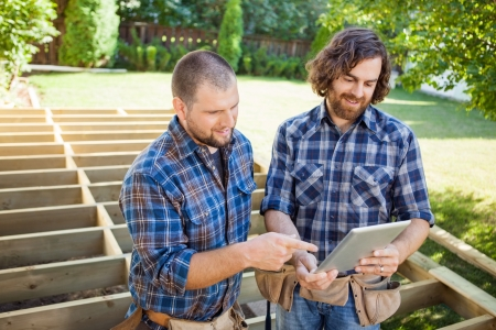 Mid adult construction worker pointing at digital tablet while discussing project with coworker photo