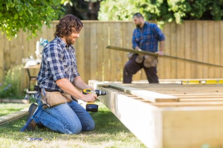 肉体労働者が建設現場でバック グラウンドで動作の同僚と木材を掘削