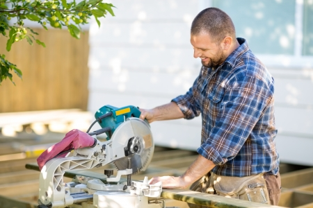 Happy mid adult carpenter cutting wood using table saw at construction site photo