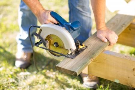 circular saw: Detail of circular saw cutting piece of wood Stock Photo