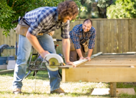 Mid adult carpenter looking at coworker while assisting him in cutting wood with handheld saw Stock Photo