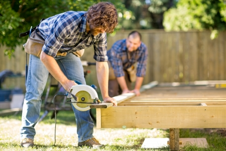 home improvements: Mid adult carpenter cutting wood with handheld saw while coworker helping him in background at construction site Stock Photo
