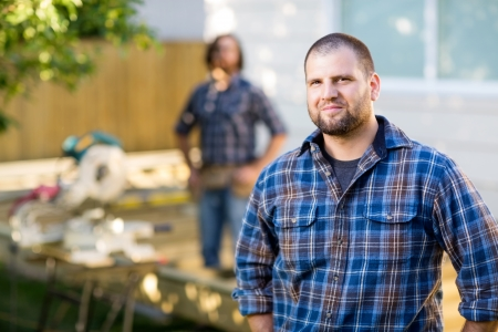 Portrait of mid adult manual worker in casual shirt standing with coworker in background at construction site photo