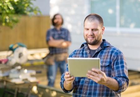 건설 현장에서 백그라운드로 서 동료와 함께 디지털 태블릿을 사용하는 성인 중반 목수 스톡 콘텐츠