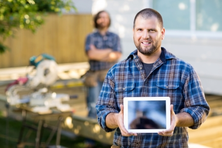 Portrait of mid adult carpenter displaying digital tablet with coworker in background at construction site photo