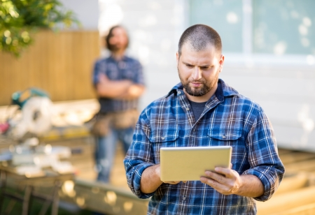 Mid adult manual worker using digital tablet with coworker standing in background at construction site photo