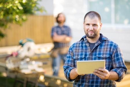 建設現場でバック グラウンドに立っている同僚とデジタル タブレットを保持している半ば大人の手動労働者の肖像 写真素材