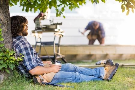 taking a break: Carpenter taking a break while coworker works in background