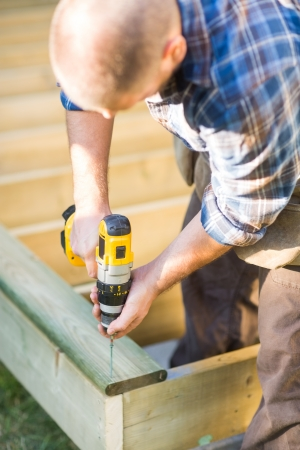 cordless: Carpenter using cordless drill while building deck Stock Photo