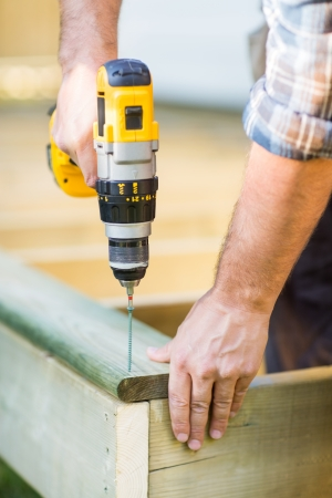 perfectionist: Cropped image of carpenters hands using drill on wood at construction site Stock Photo