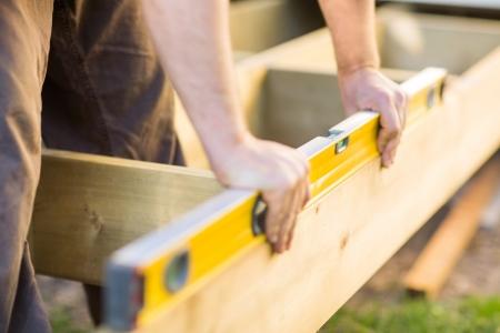 menuisier: Image recadr�e du niveau de contr�le de mains charpentier de bois au chantier de construction