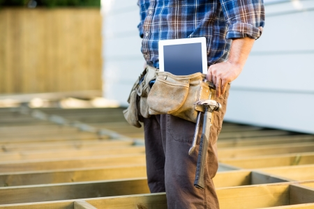 Midsection of construction worker with tablet computer and hammer in toolbelt at site photo