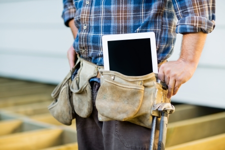 Midsection of construction worker with tablet computer in toolbelt at site Stock Photo