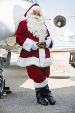 Full length portrait of Santa leaning on private jet at airport terminal