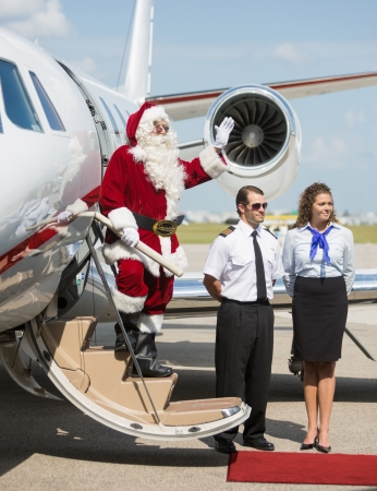 Full length of Santa waving hand on ladder of private jet. photo