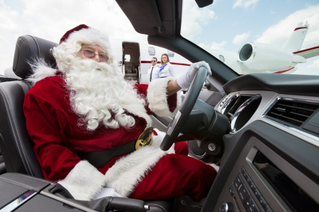 Portrait of Santa driving convertible with pilot and airhostess standing in background at airport terminal photo