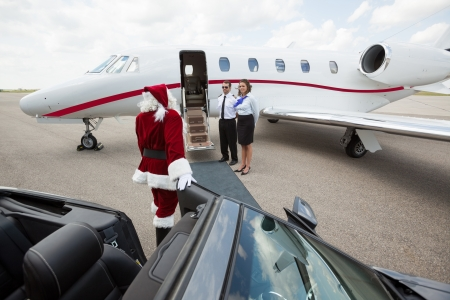 Santa leaving convertible car and walking up to jet photo