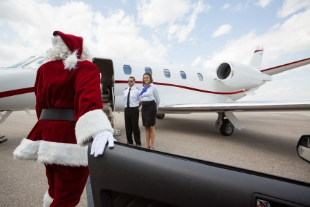 disembarking: Santa disembarking car while walking towards private jet with pilot and airhostess standing by