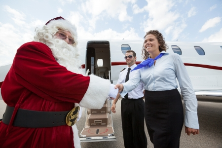 Airhostess and Pilot welcoming Santa against private jet at airport terminal photo