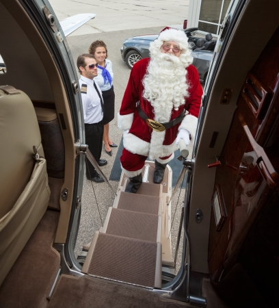 Portrait of Santa boarding private jet with stewardess and captin standing in background photo