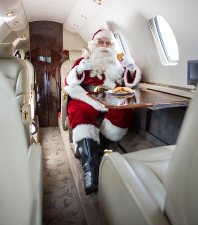 Man in Santa costume having cookies and milk in private jet photo